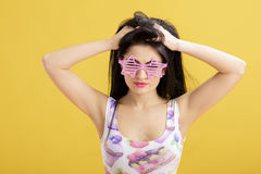 Attractive young brunette woman in pink skirt and tank top on yellow background. funny girl with pink sunglasses Royalty Free Stock Images