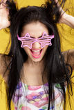 Attractive young brunette woman in pink skirt and tank top on yellow background. funny girl with pink sunglasses Royalty Free Stock Photos