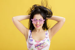Attractive young brunette woman in pink skirt and tank top on yellow background. funny girl with pink sunglasses Stock Images