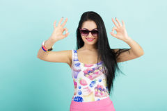 Attractive young brunette woman in pink tank top on blue background.  girl in sunglasses showing OK sign Stock Photography