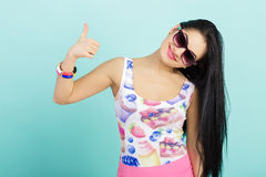 Attractive young brunette woman in pink tank top on blue background.  girl in sunglasses showing thumbs up Stock Photo