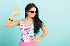 Attractive young brunette woman in pink tank top on blue background. girl in sunglasses shows five fingers Royalty Free Stock Photos