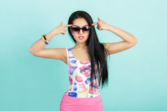 Attractive young brunette woman in pink tank top on blue background. smilling girl in sunglasses Royalty Free Stock Photos