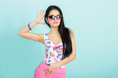 Attractive young brunette woman in pink tank top on blue background. smilling girl in sunglasses Stock Image