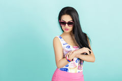 Attractive young brunette woman in pink tank top on blue background. smilling girl in sunglasses Royalty Free Stock Photography