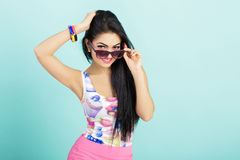 Attractive young brunette woman in pink tank top on blue background. woman looks out from under glasses at camera. Attractive young brunette woman in pink tank Royalty Free Stock Photo