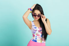 Attractive young brunette woman in pink tank top on blue background. woman looks out from under glasses at camera. Attractive young brunette woman in pink tank Stock Photos