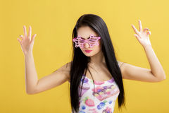 Attractive young brunette woman in pink tank top on yellow background. funny girl with pink sunglasses dancing Stock Photo