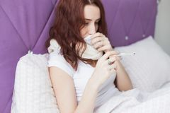 An attractive young brunette woman sits in her bed with a thermometer. Colds and home treatment stock photos