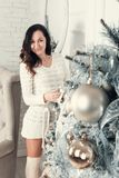 Attractive young brunette woman standing near fir tree in Christ Stock Images