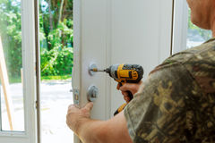 Attractive young builder is installing lock in door. He is holding a screwdriver and kneeling. Royalty Free Stock Photos