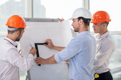 Attractive young builders are blueprinting a new Royalty Free Stock Photos