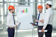 Attractive young builders are discussing the. Cheerful architect is explaining to his team the main ideas of construction. He is pointing at blueprint with royalty free stock image