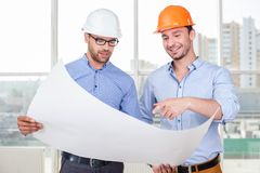 Attractive young builders are watching the Royalty Free Stock Photo