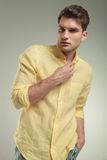 Attractive young business man closing his yellow shirt. Royalty Free Stock Photography