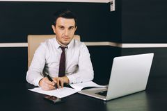 Attractive business man in smart casual wear sitting at his working place in office royalty free stock photography