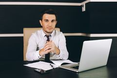 Attractive business man in smart casual wear sitting at his working place in office stock image