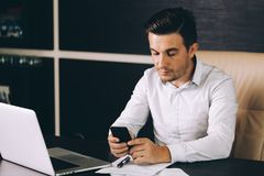 Attractive business man in smart casual wear sitting at his working place in office holding a smart phone royalty free stock photo