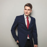 Attractive young business man smiling. While holding his hand in the back pocket Royalty Free Stock Images