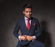Attractive young business man unbuttoning his jacket. While looking away from the camera Royalty Free Stock Photography