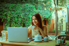 Attractive young business woman with laptop on table and cup of. Tea in hands smiling on camera outdoors Stock Images