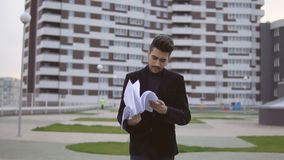 Attractive young businessman in black suit throw out documents outdoor.  stock video footage