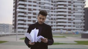 Attractive young businessman in black suit throw out documents outdoor against office building. stock video footage
