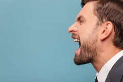 Attractive young businessman is expressing his. Close up of face of man shouting with anger. He is standing in profile. Isolated on blue background. Copy space Stock Images
