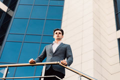 Attractive young businessman in front of a modern office building on a beautiful sunny day. Attractive young businessman in front of a modern office building on stock photography