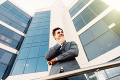 Attractive young businessman with hands on chin in front of a modern office building on a beautiful sunny day. Attractive young businessman in front of a modern royalty free stock photo