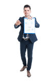 Attractive young businessman holding clipboard with financial di Stock Images