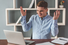 Attractive young businessman. Is lifting hands in dismay while working with a laptop in office stock image