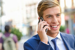 Attractive Young Businessman On The Phone In Urban Background Stock Photos