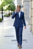 Attractive young businessman on the phone in urban background Stock Images