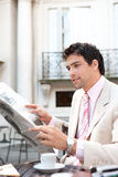 Attractive businessman reading paper in cafe. Stock Images