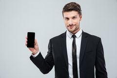 Attractive young businessman showing blank screen cell phone. Over white background royalty free stock image