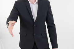 Attractive young businessman standing and giving his hand for ha Royalty Free Stock Image