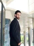 Attractive young businessman standing outside office building Royalty Free Stock Photo
