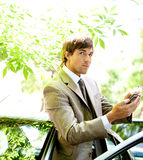 Businessman with car and smartphone. Royalty Free Stock Photography