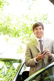 Businessman with car and smartphone. Royalty Free Stock Images