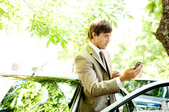 Businessman with car and smartphone. Royalty Free Stock Photo