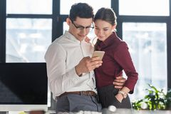 Attractive young businesspeople in formal clothing having office romance and using. Smartphone together stock photography