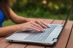 Attractive young businesswoman focused on her work looking at laptop screen sitting in park. Stock Image