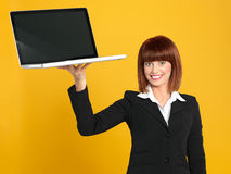 Attractive, young businesswoman holding a laptop. Funny portrait of a beautiful, young businesswoman, holding a laptop as a tray, smiling, on yellow background stock photography