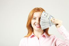 Attractive young businesswoman posing with bunch of USD cash in hands showing positive emotions and happy facial expression. stock photo