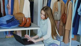 Attractive young businesswoman is sitting and talking on mobile phone while working with laptop in her clothing store. Attractive young businesswoman is sitting stock video footage