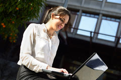 Attractive young businesswoman typing in a laptop computer, urba Stock Photography