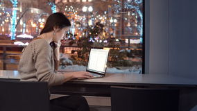 Attractive young businesswoman working on laptop sitting at the bar, outside winter night city decorated for Christmas stock footage