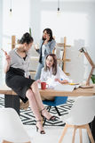 Attractive young businesswomen in formal wear working together in modern office Stock Photos
