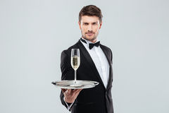 Attractive young butler in tuxedo offers you glass of champagne. Attractive young butler in tuxedo with bow tie offers you glass of champagne Royalty Free Stock Photography